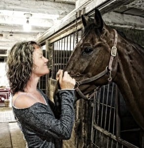 Krista and one of the horses in the barn.